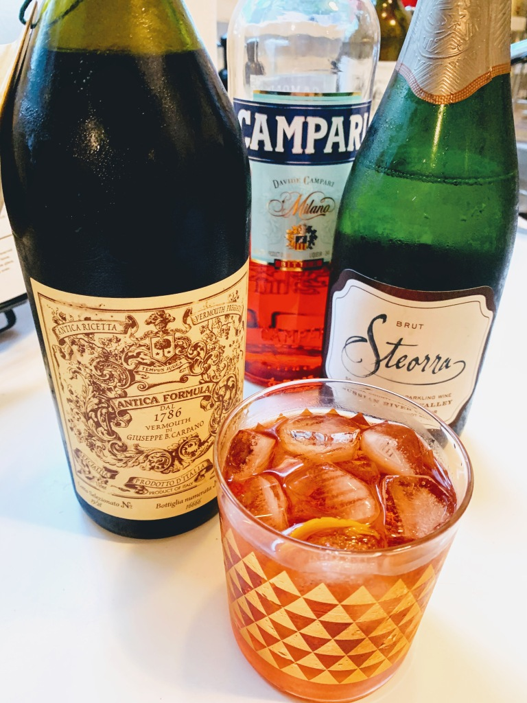 A bottle of vermouth, Campari and prosecco and a cocktail