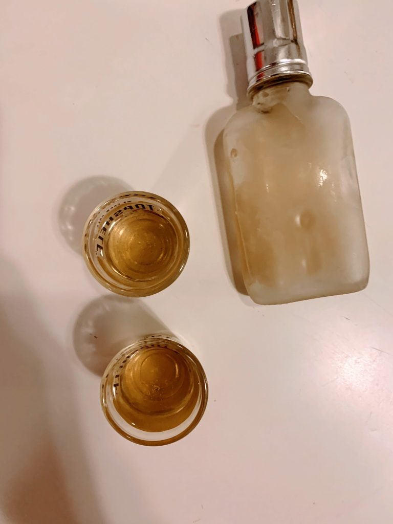 A small bottle of liquor and two filled shot glasses