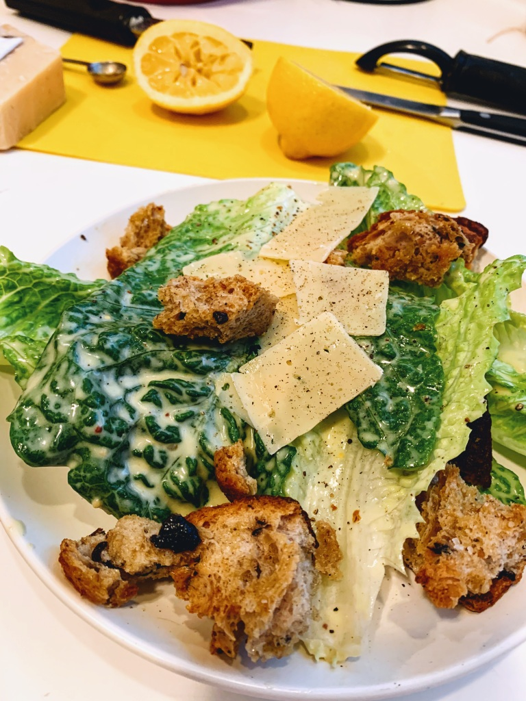 A caesar salad with cut lemon halves in the background