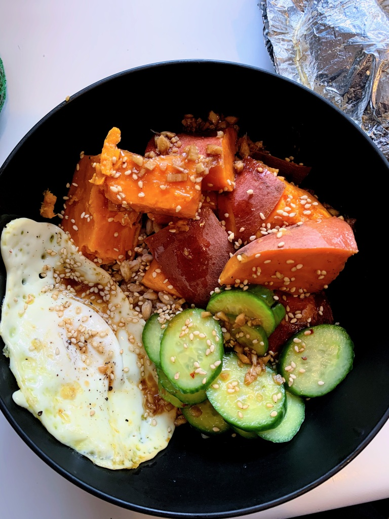 Grain bowl of farro, sweet potato, cucumber & a fried egg.