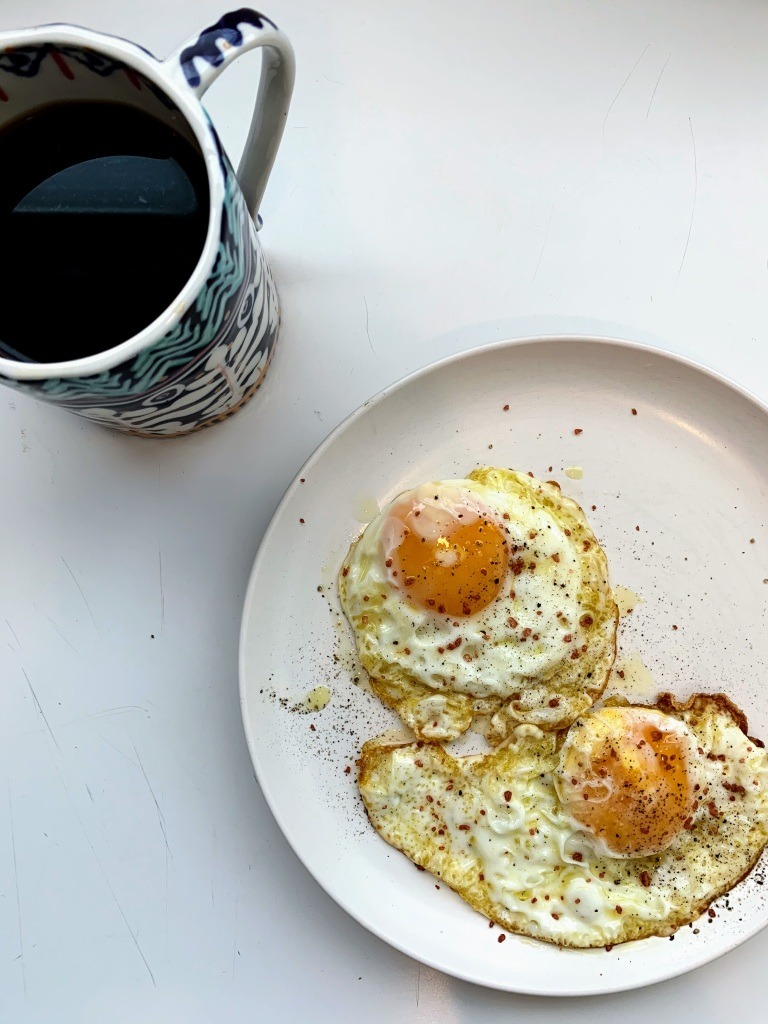 Two fried eggs & a cup of coffee.