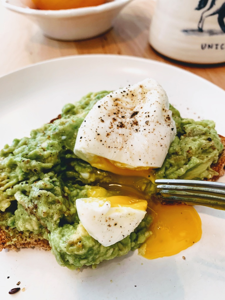 Smashed avocado toast with a runny poached egg cut open on top