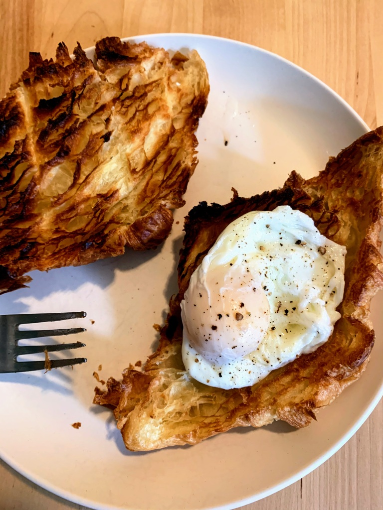Toasted croissant halves with a poached egg on top.