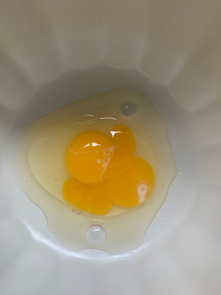 One cracked egg in a bowl with two yolks.