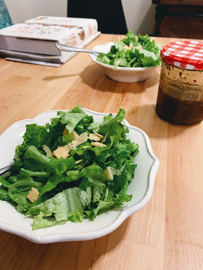Two bowls of salad and a glass jar of dressing