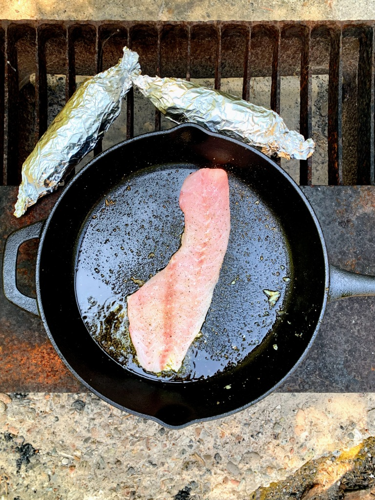 Cooking rockfish in a cast-iron skillet  with 2 tin-foil-wrapped ears of corn