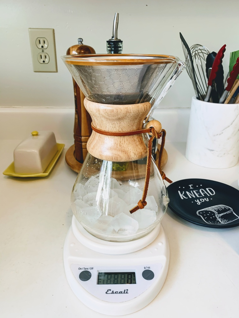 Chemex brewer filled with ice sitting on a kitchen scale